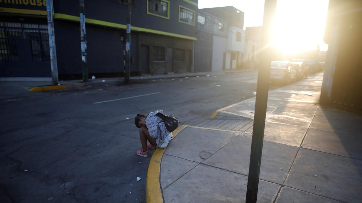 Une femme est assise sur le trottoir d'une rue déserte.