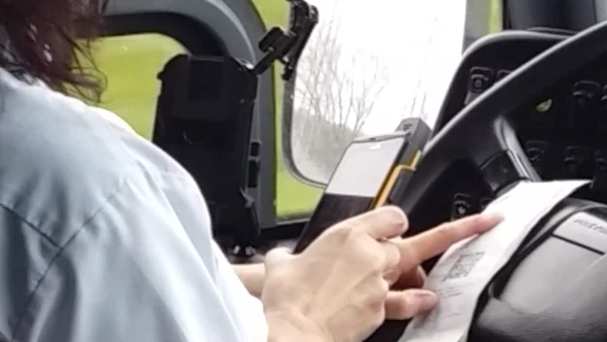 Une employée de Limocar manipule un lecteur optique en conduisant.