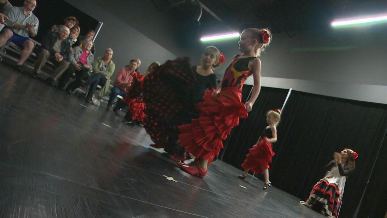 Des jeunes dansent du flamenco en avant-plan. Lina Kazan applaudit de façon rythmique en arrière-plan.