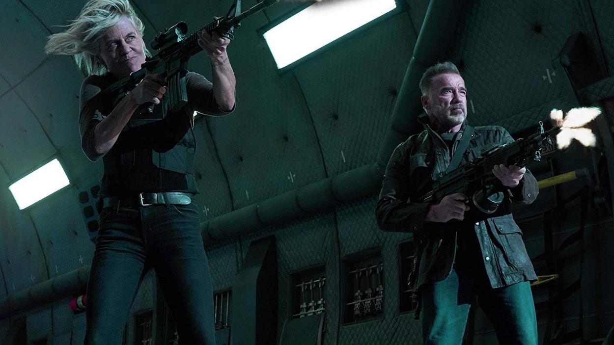 Les deux acteurs tiennent de grosses armes à feu.
