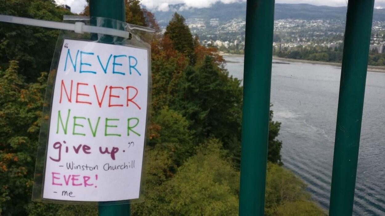 Un message écrit à la main où on peut lire Never, never, never give up, ever. installé sur le pont Lions Gate.
