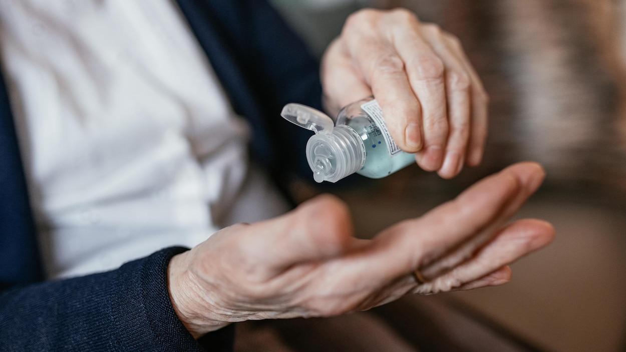 Une femme âgée se verse du liquide désinfectant sur la main.