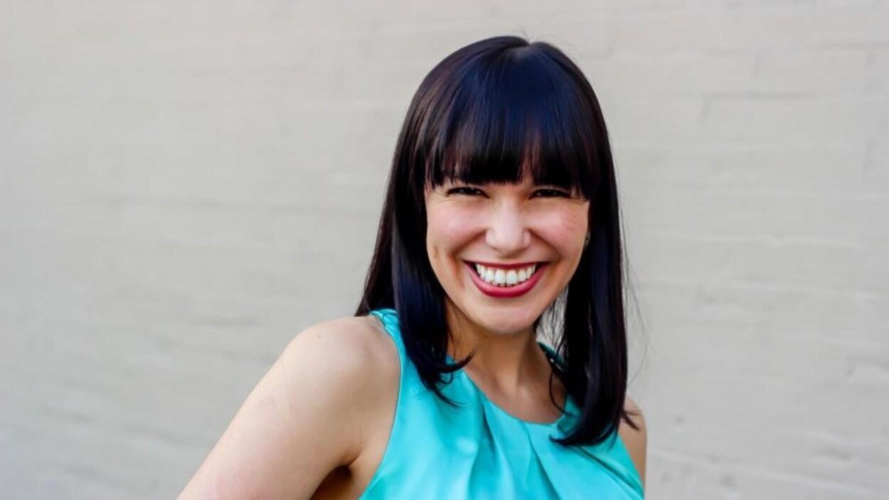 La jeune femme aux cheveux noirs de jais affiche un immense sourire, elle arbore une frange.