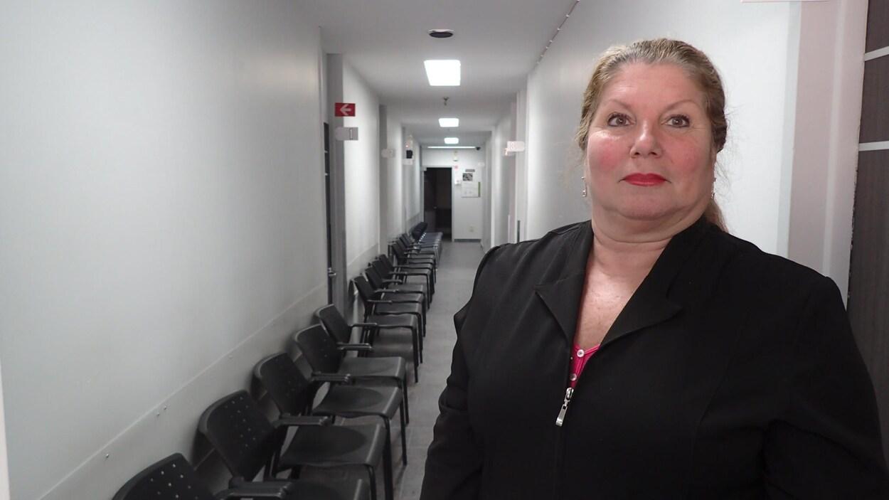 La propriétaire et directrice de la Polyclinique médicale populaire cherche depuis 6 mois un ou des médecins. Elle pose devant un long corridor rempli de chaises vides.