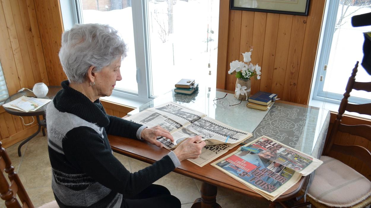 Mme Boudrias consulte des journaux étalés sur une table.