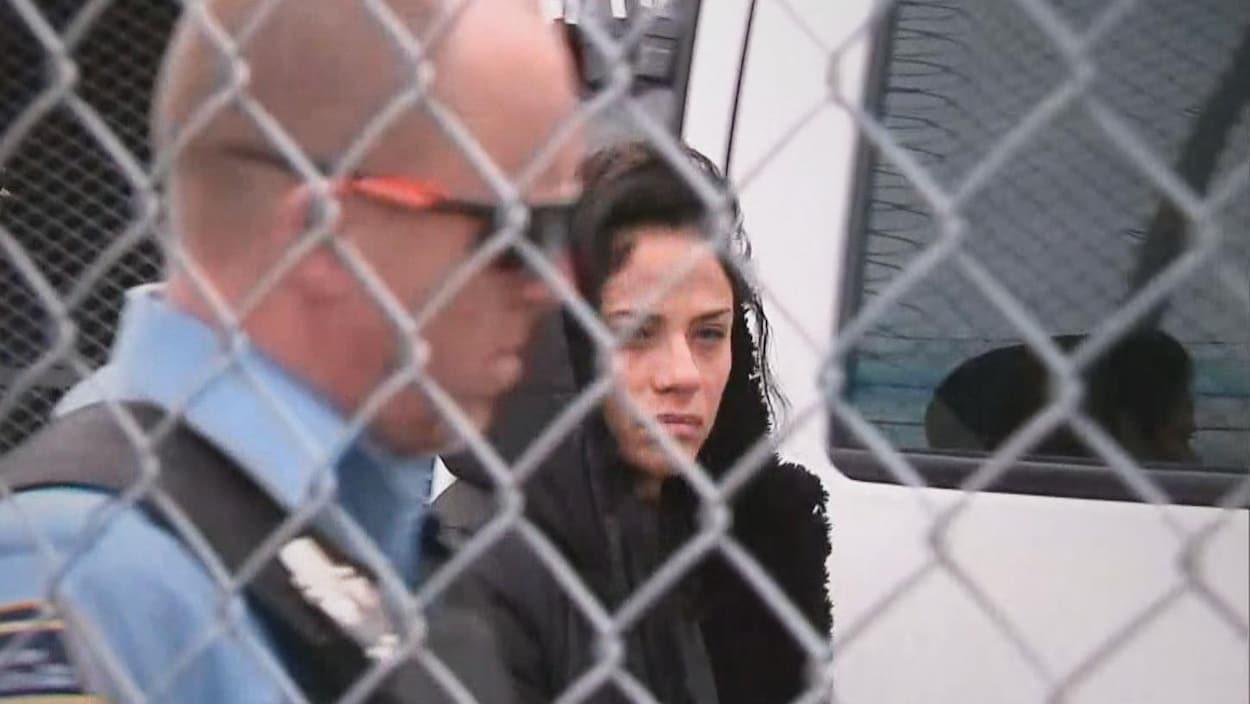 Lison Asselin est escortée par un constable spécial à son arrivée au palais de justice de La Malbaie.