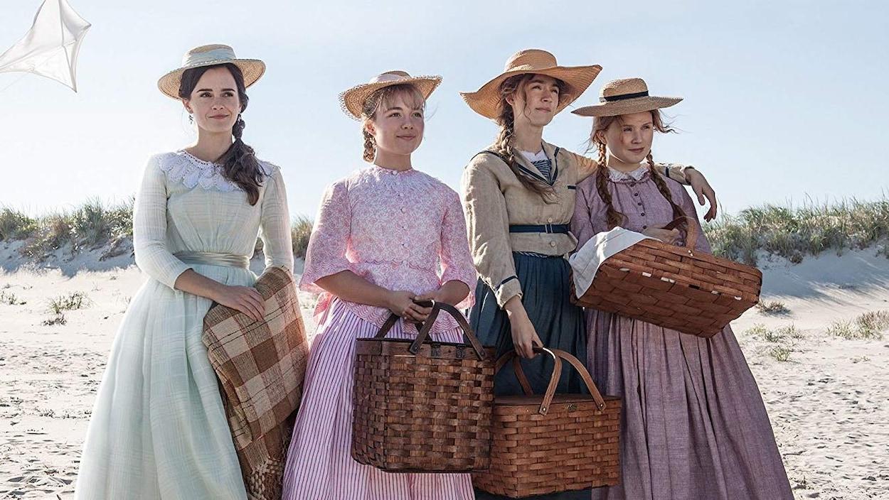 Quatre jeunes femmes portant des vêtements d'époque se trouvent sur une plage et tiennent le nécessaire pour faire un pique-nique.
