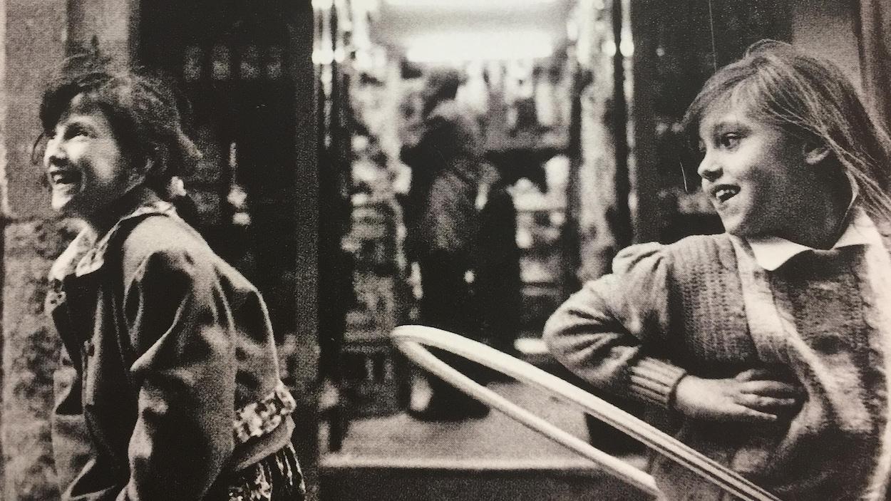 Sur une image d'apparence ancienne, deux jeunes filles sourient.