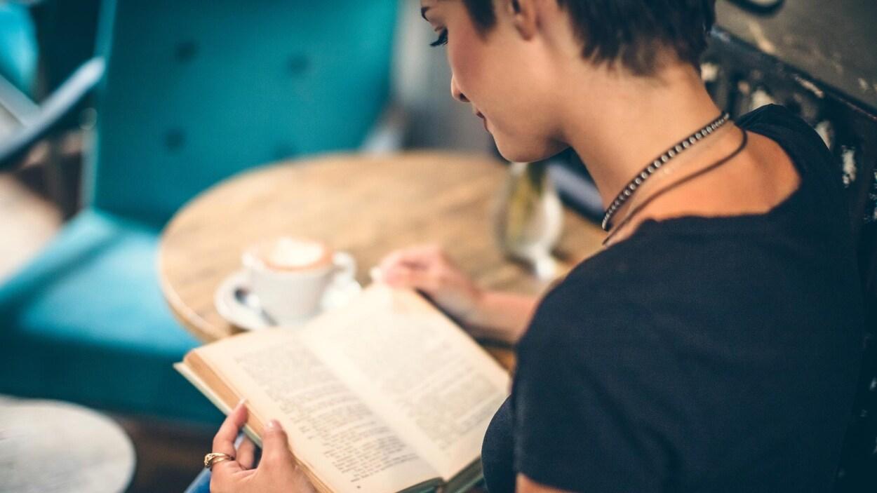 Une jeune femme vue de dos lit un livre dans un café.