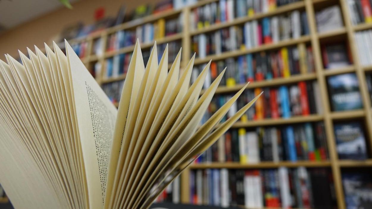 En avant-plan un livre ouvert, en arriere-plan une bibliotheque.