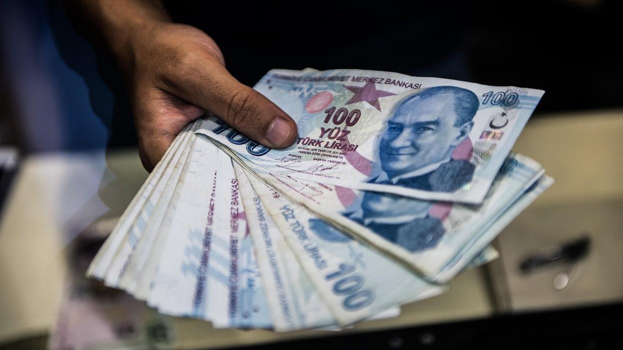 Un homme tient dans sa main des billets de 100 livres turques.
