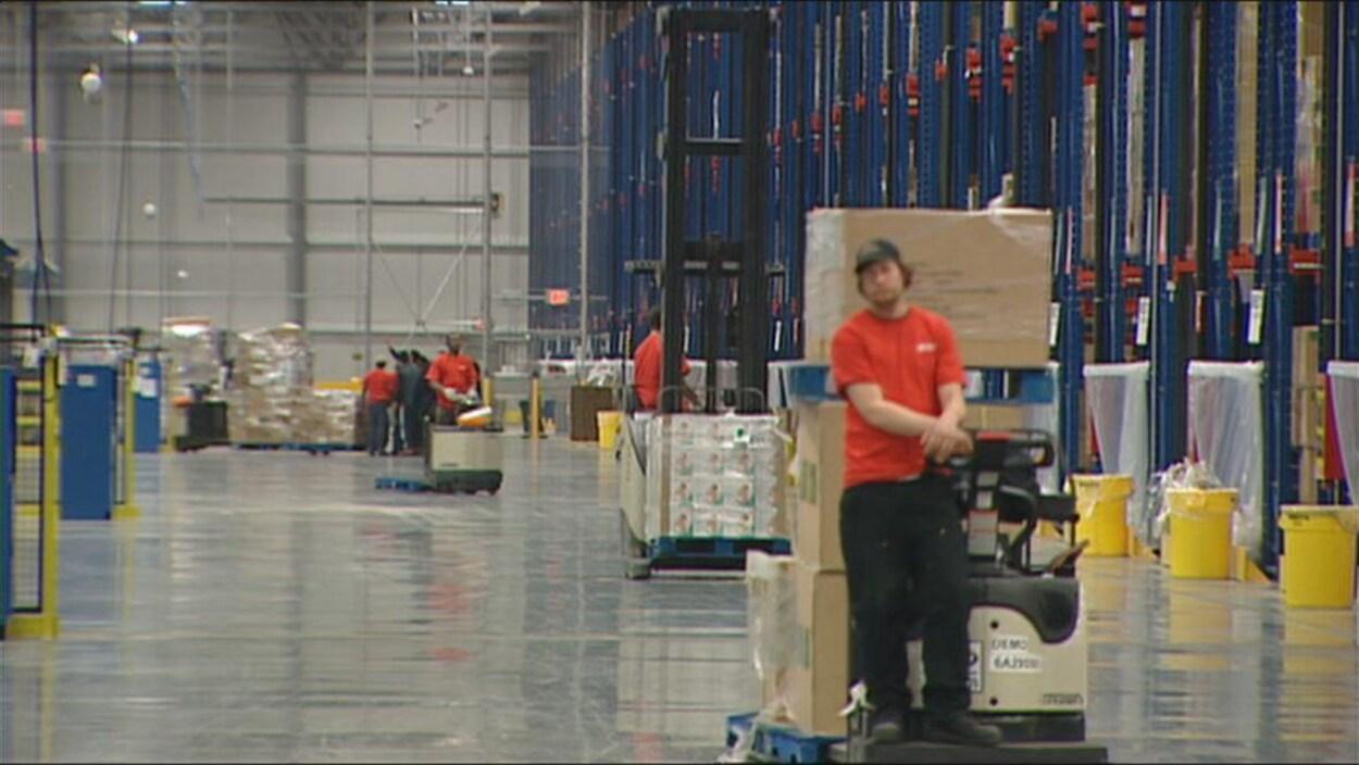 Un entrepôt où des personnes travaillent en déplaçant des cartons.