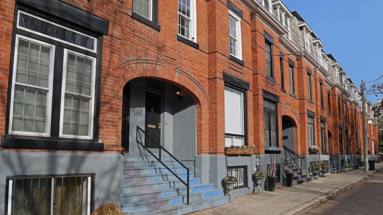 Une rangée de façades en briques orange donnant sur un long trottoir.