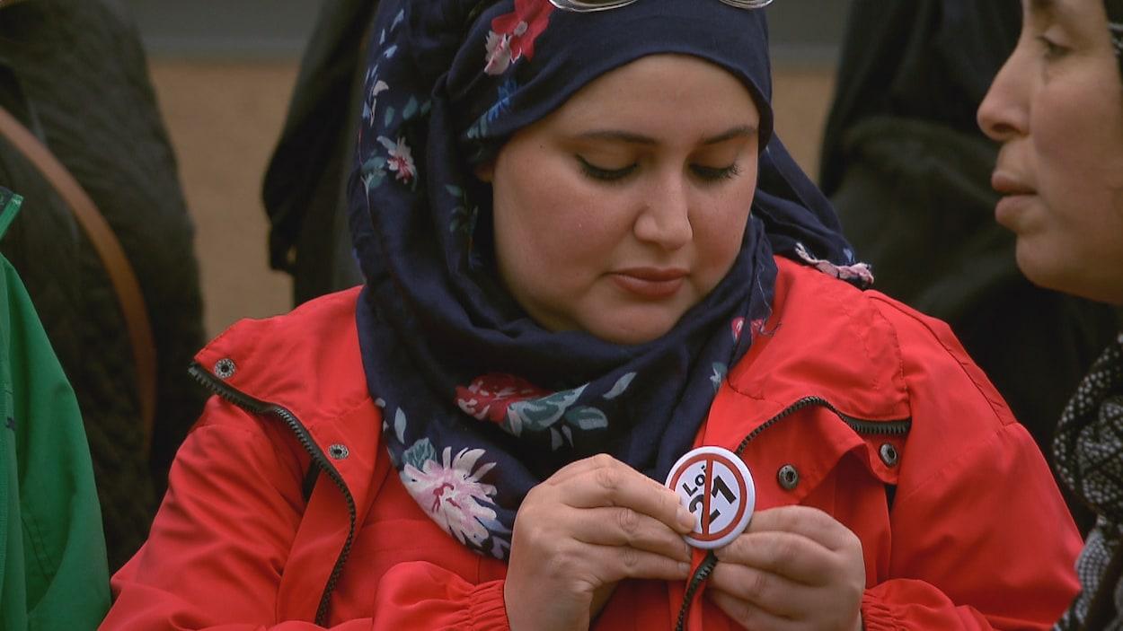 Une manifestante portant le voile épingle sur son manteau rouge un macaron sur lequel les mots « Loi 21» sont biffés.