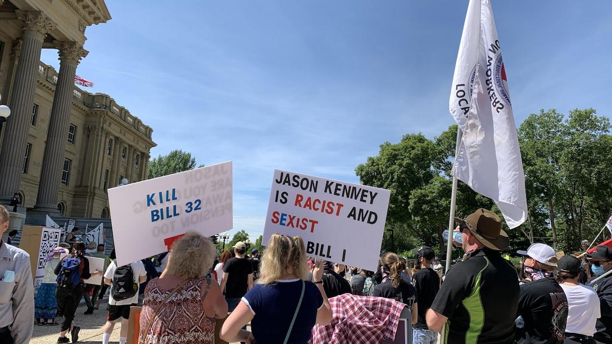 Des manifestants tiennent des pancartes et des drapeaux devant l'Assemblée législative.