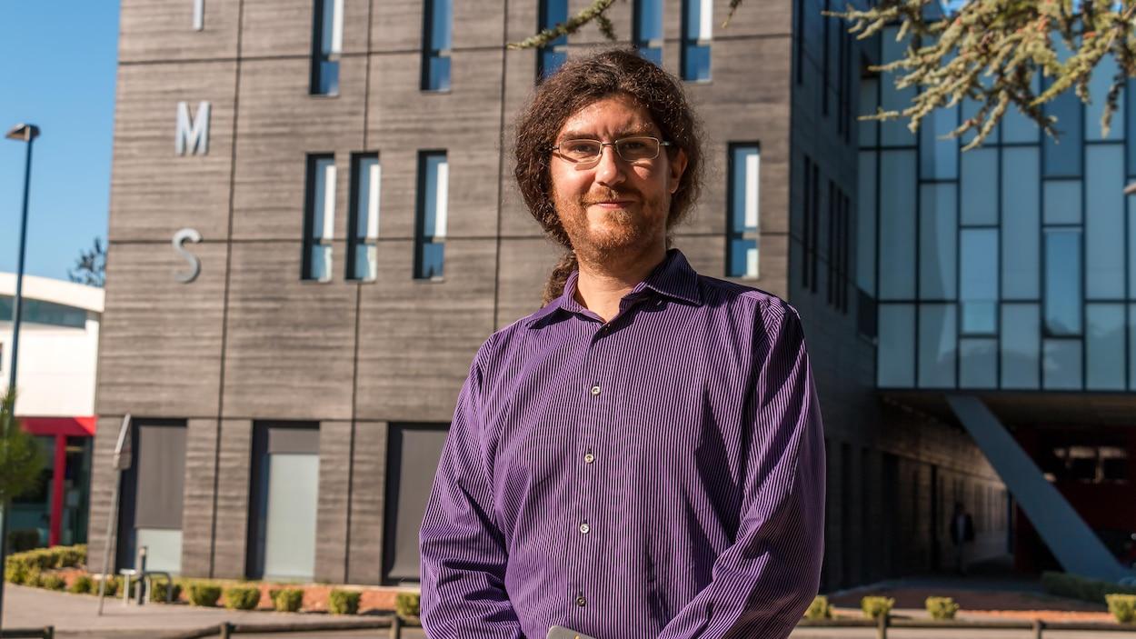 Loïc Boulon devant une bâtisse sur laquelle on peut lire IMS.