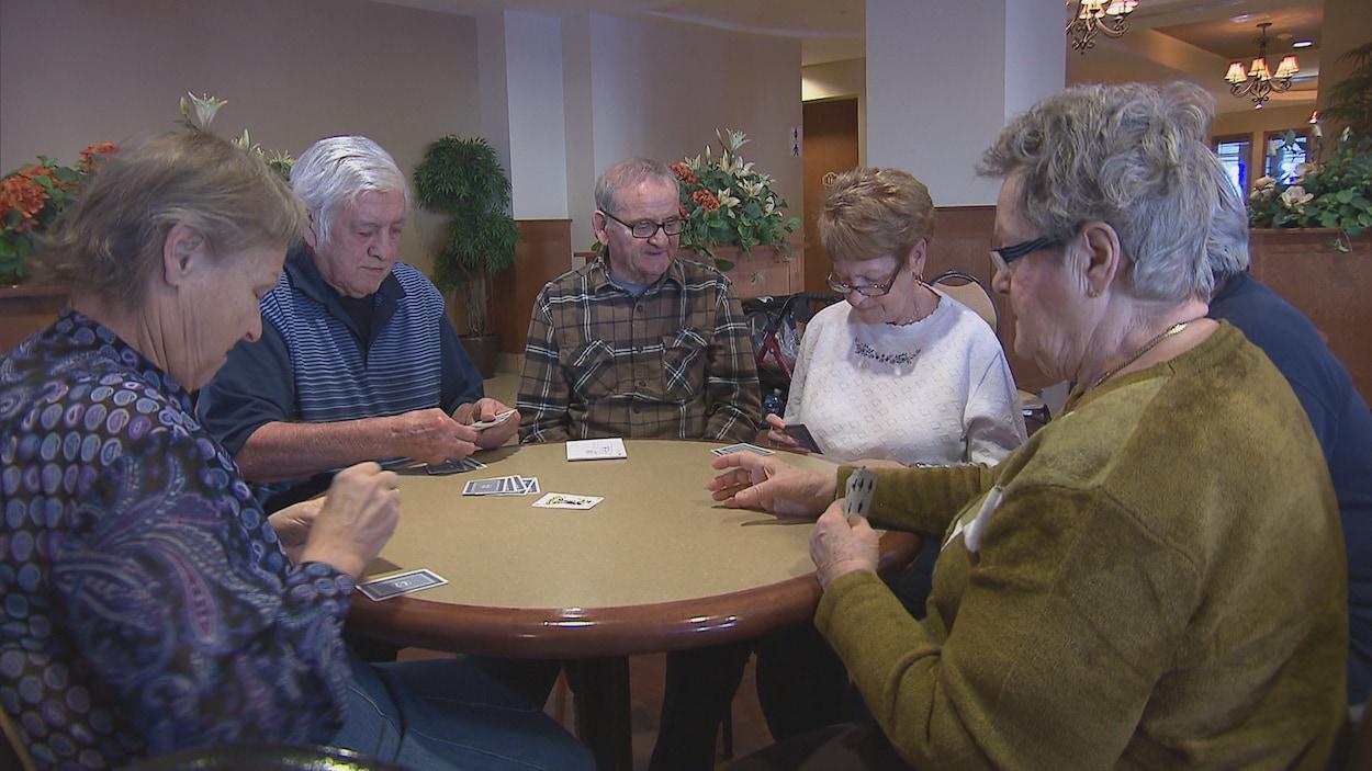 Des personnes âgées jouent aux cartes.