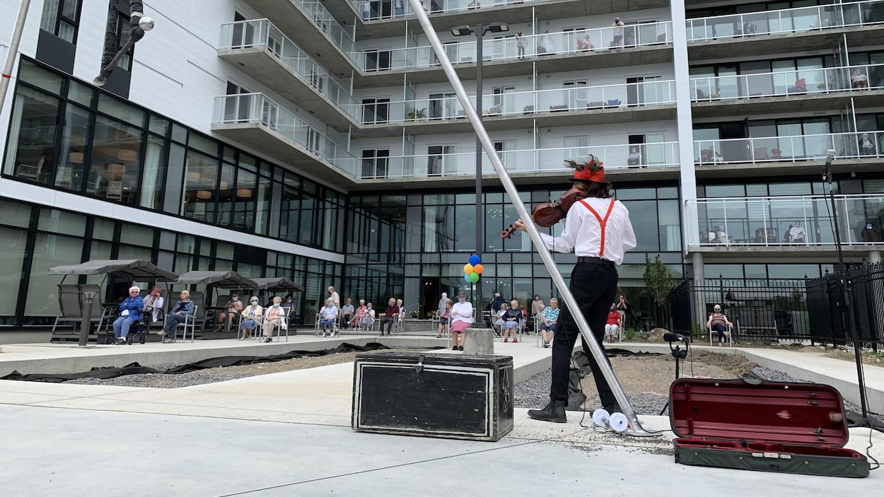 Un clown humanitaire joue du violon devant une résidence pour personnes âgées.