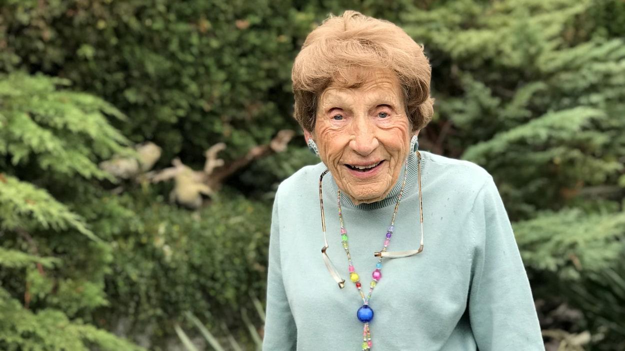 Une femme âgée qui sourit. Elle porte un col roulé vert pâle.