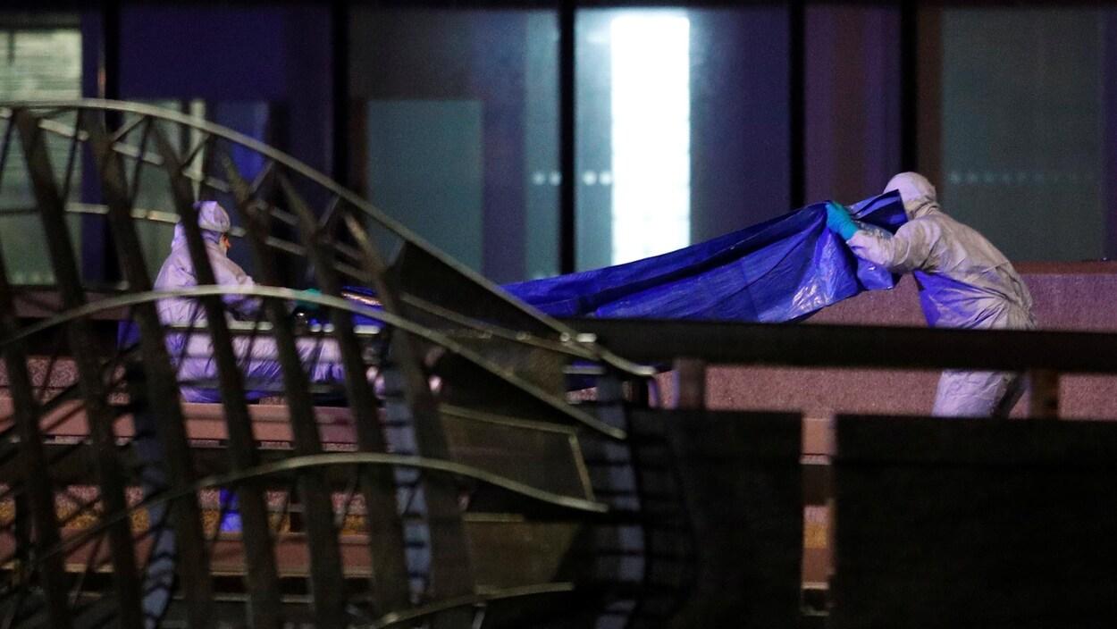 Deux travailleurs en combinaison manipulent une bâche sur un pont.
