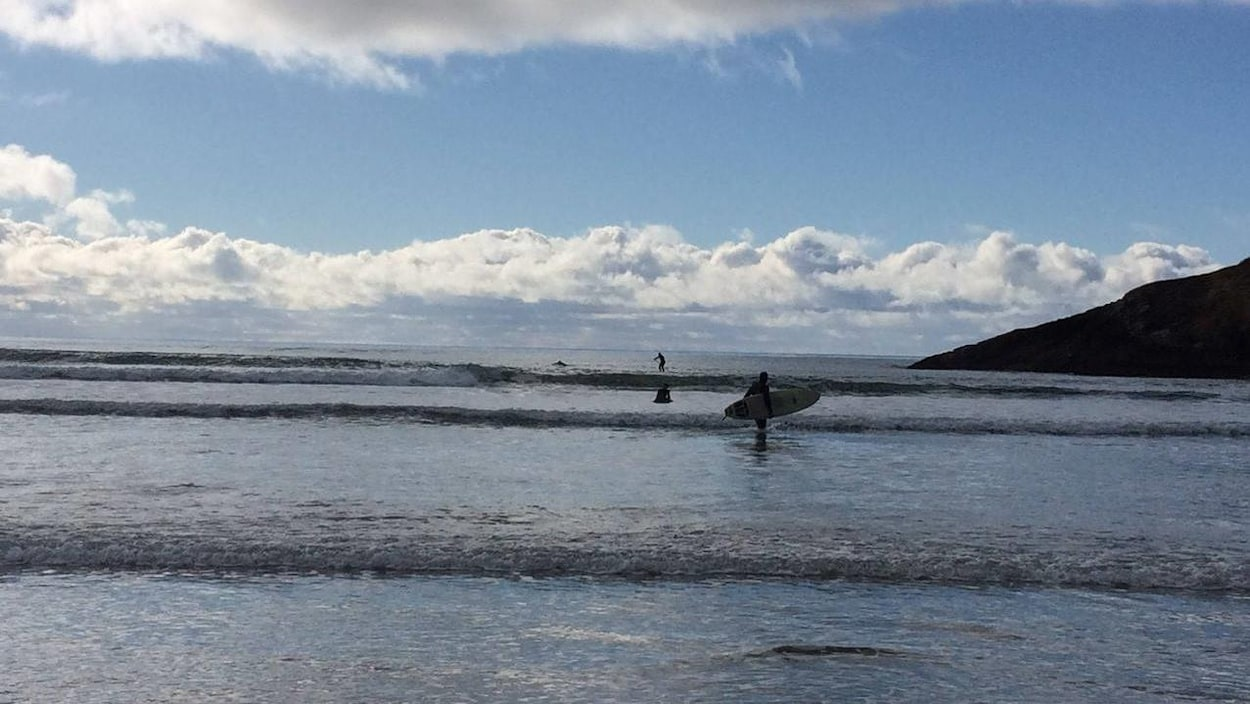 Un homme tient sa planche de surf debout dans l'eau alors que des vagues déferlent sur le rivage. Deux autres surfeurs au loin, un debout, un assis sur sa planche.