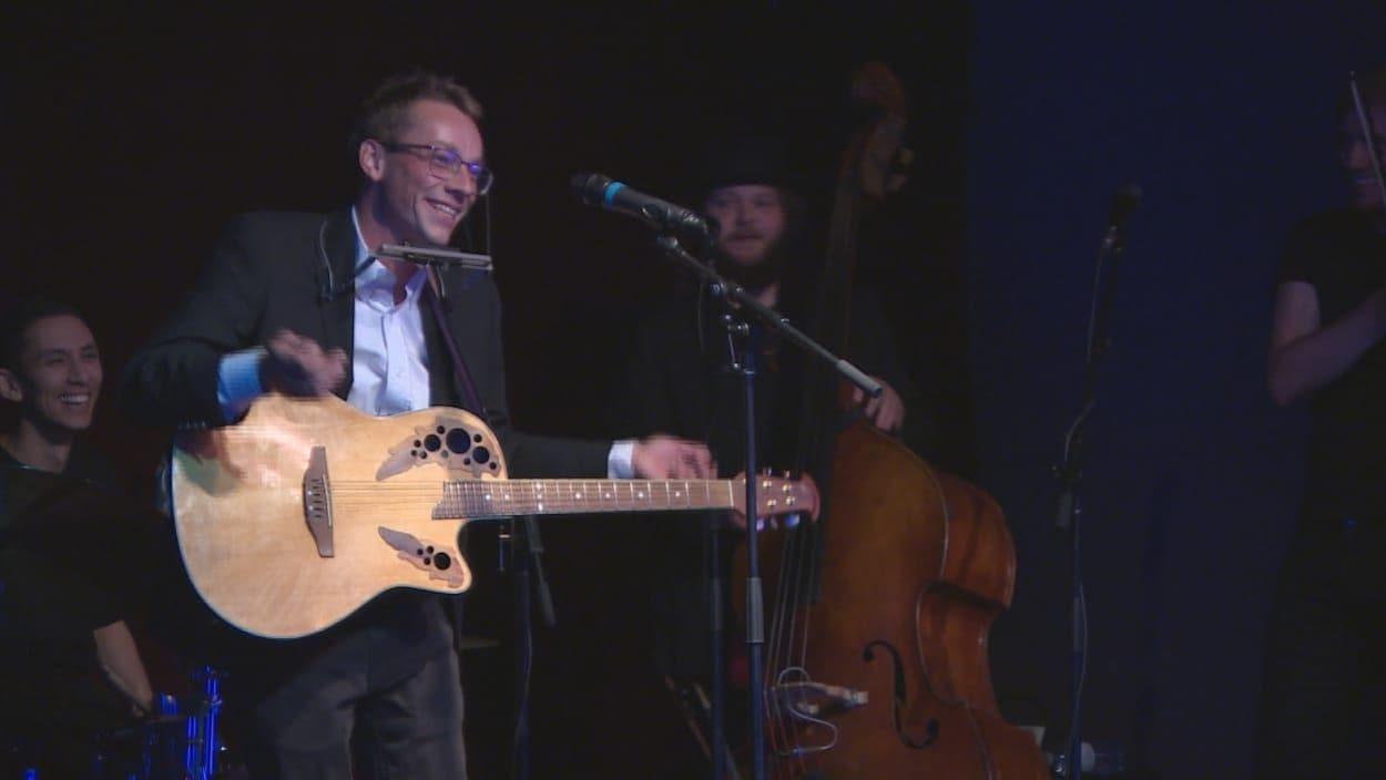Lord Byrun sur scène devant un microphone, tenant une guitare et un harmonica.