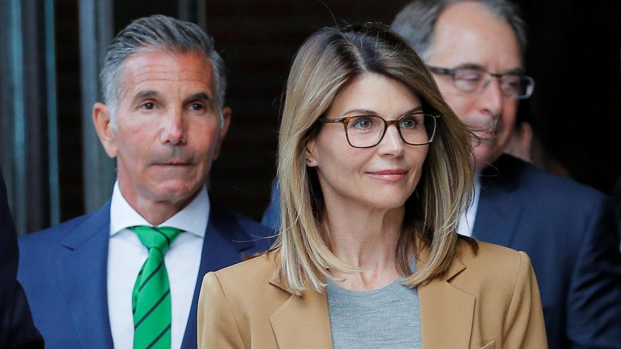 En premier plan, une femme portant des lunettes rectangulaires sourit. En arrière, un homme au regard sérieux la suit.