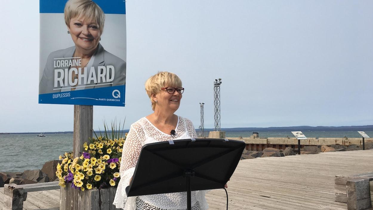 La députée sortante et candidate du Parti québécois dans Duplessis, Lorraine Richard, s'adresse aux médias avec en arrière-plan le Vieux-Quai de Sept-Îles et un bateau au large.