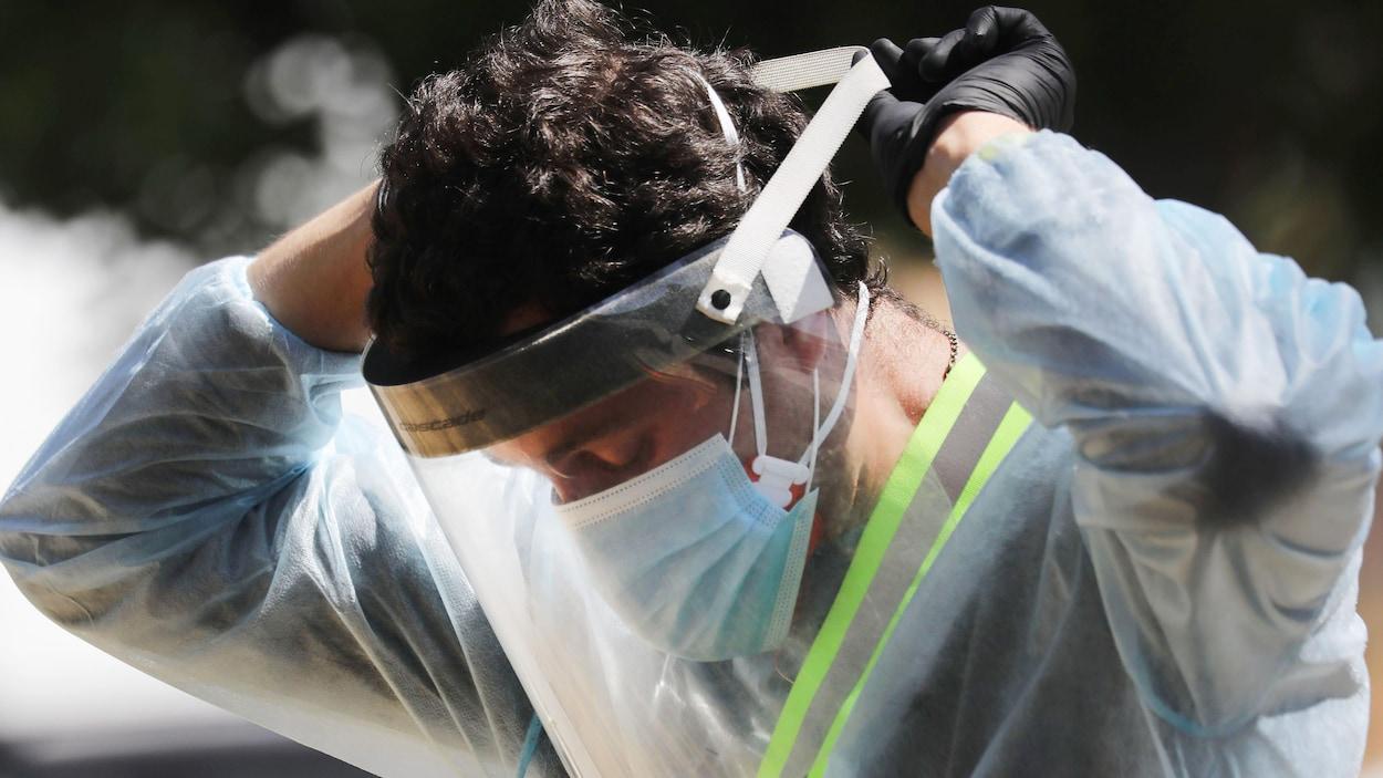 Un homme qui porte une blouse de protection et un masque ajuste sa visière.