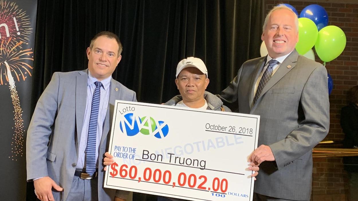 Trois hommes tiennent un gros chèque sur lequel est écrit 60 000 002 $.