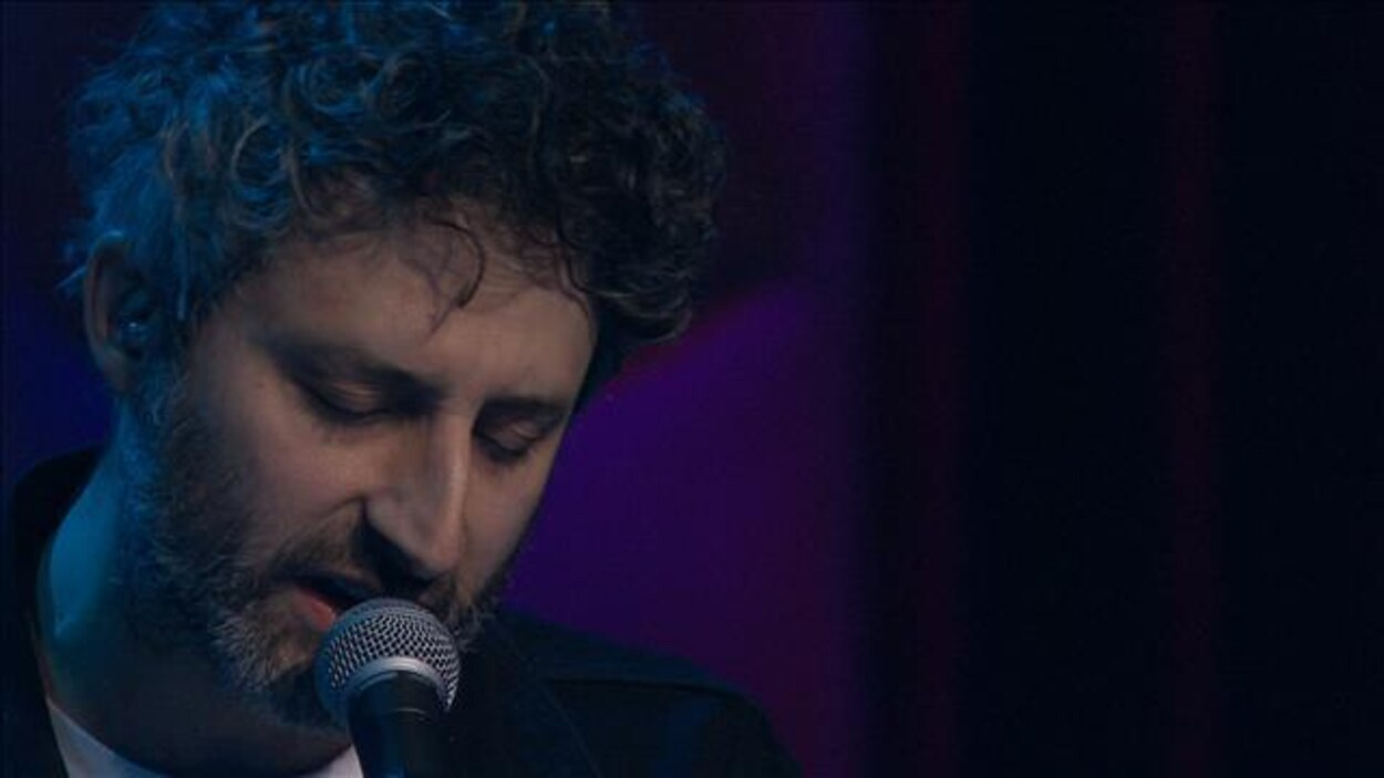 Un homme chante dans un micro.