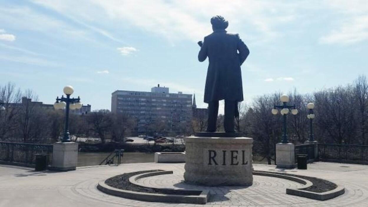 La statue à l'effigie de Louis Riel devant une rivière à Winnipeg.