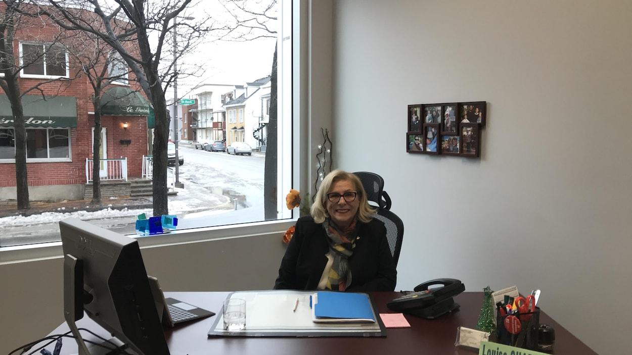 La nouvelle députée fédérale de Trois-Rivières, Louise Charbonneau, assise derrière son bureau, avec un écriteau où son nom est inscrit.