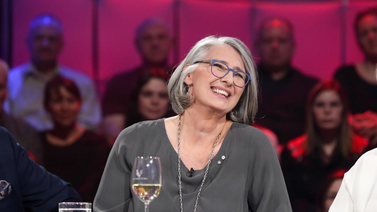 La femme sourit avec un verre de vin devant elle.