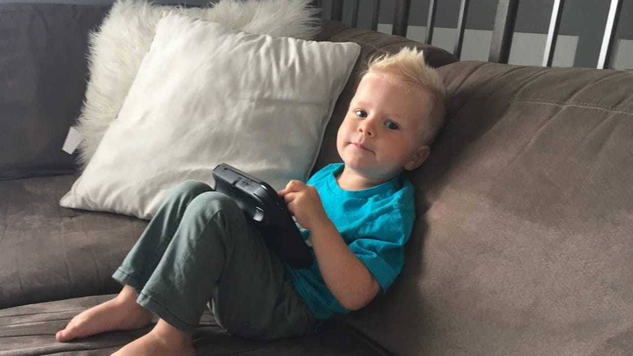 Luke Germs, 3 ans, a la taille d'un enfant de 10 mois. Il est assis sur un fauteuil et tient une manette de jeux vidéo qui semble très grosse entre ses petites mains.