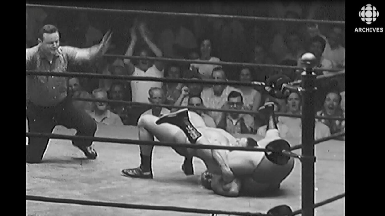 Le lutteur Edouard Carpentier maintient au sol son adversaire.