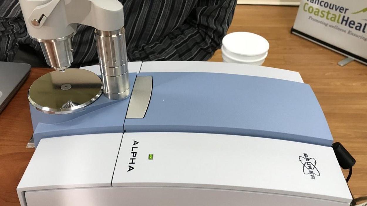 Gros plan d'un appareil de détection qui fentanyl qui ressemble à une imprimante avec un microscope par-dessus.