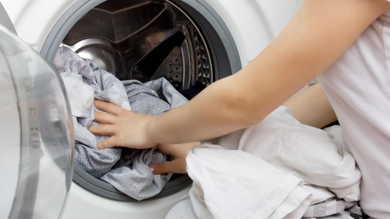 Une femme met des vêtements dans la machine à laver.