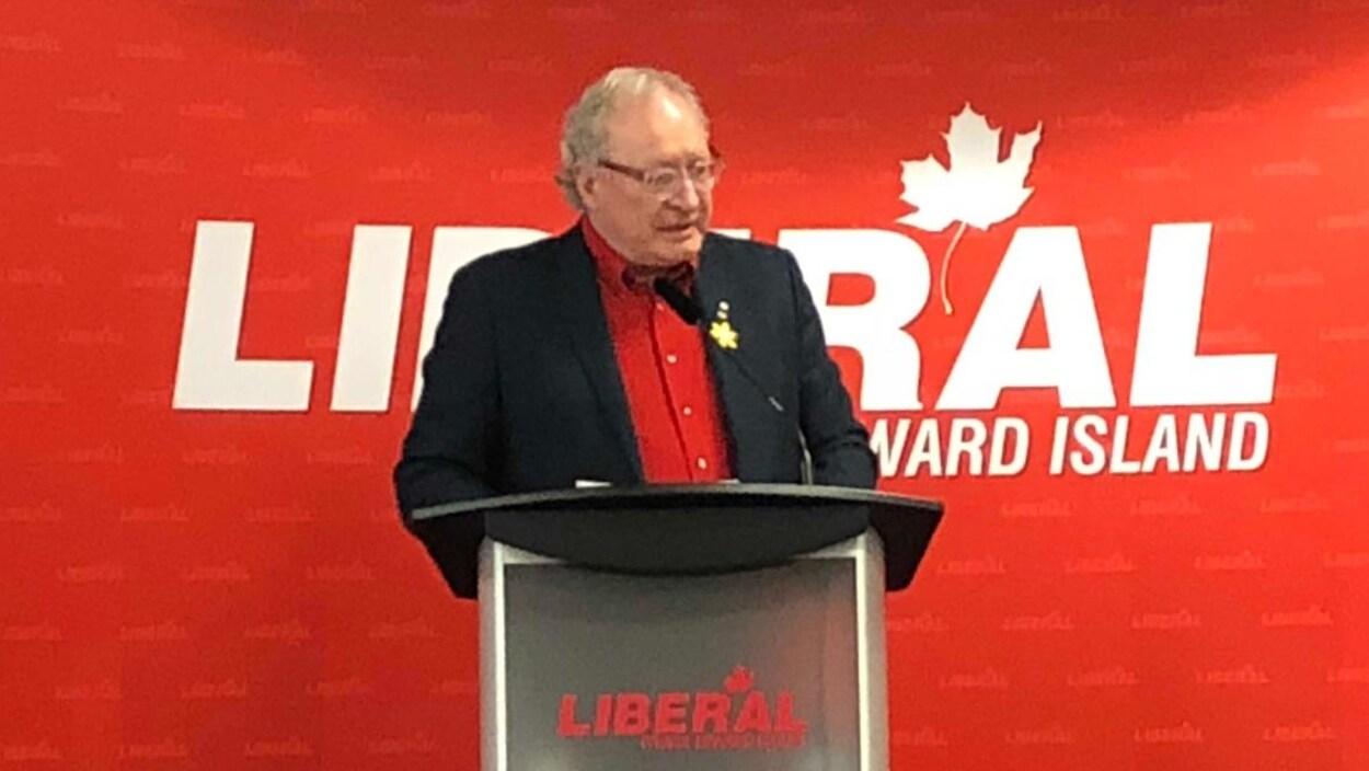 Wade MacLauchlan sur une scène devant une grande affiche du Parti libéral