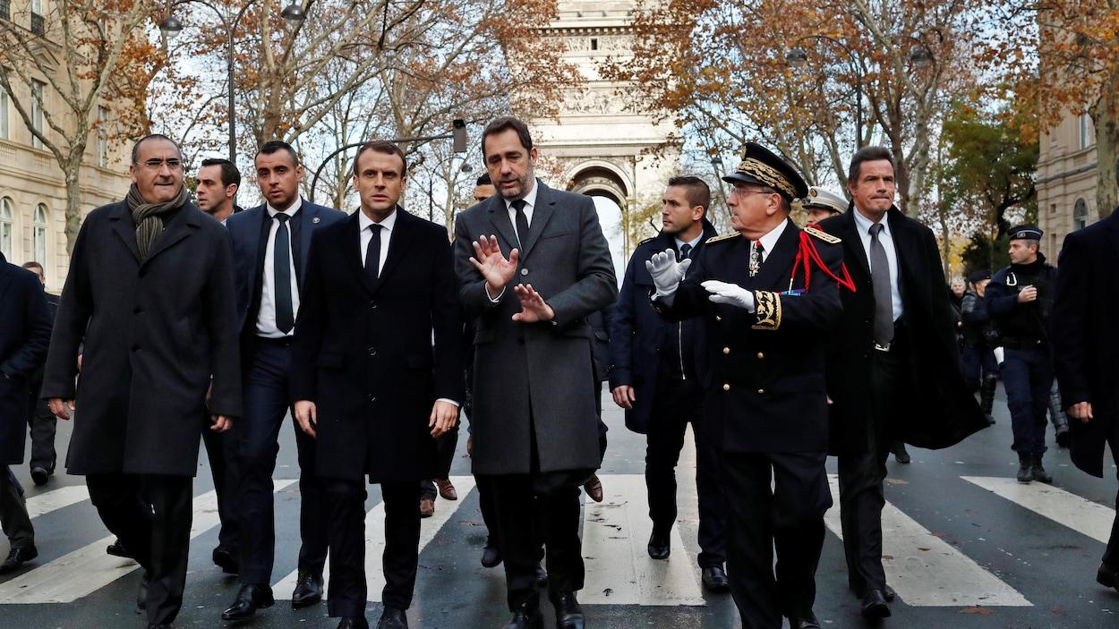 Emmanuel Macron marche dans les rues de Paris avec Christophe Castaner, le ministre de l'Intérieur et des gardes du corps. Il y a aussi un haut gradé.