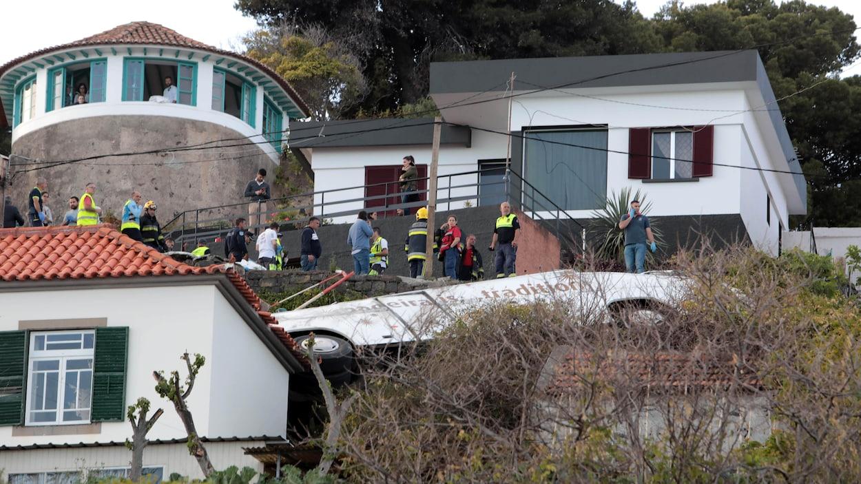 Des secouristes se tiennent à côté de l'épave d'un autocar après un accident survenu sur l'île portugaise de Madère, le 17 avril 2019.