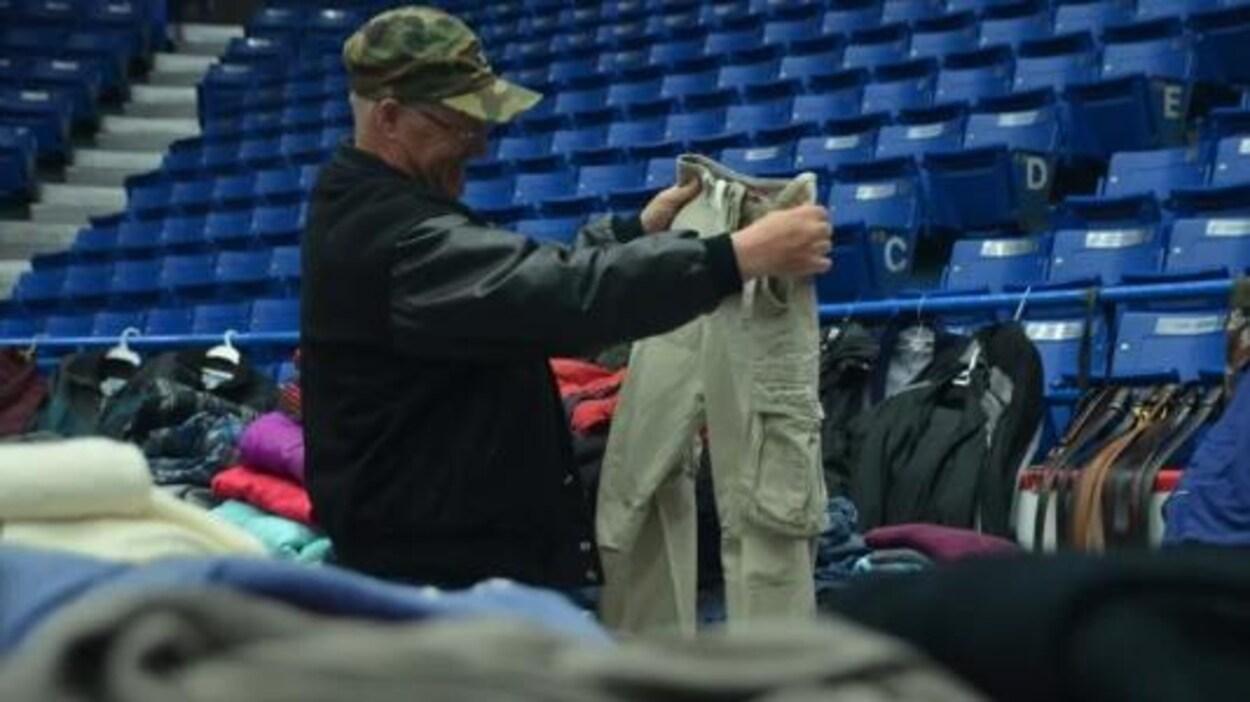 Un homme qui regarde une paire de pantalons