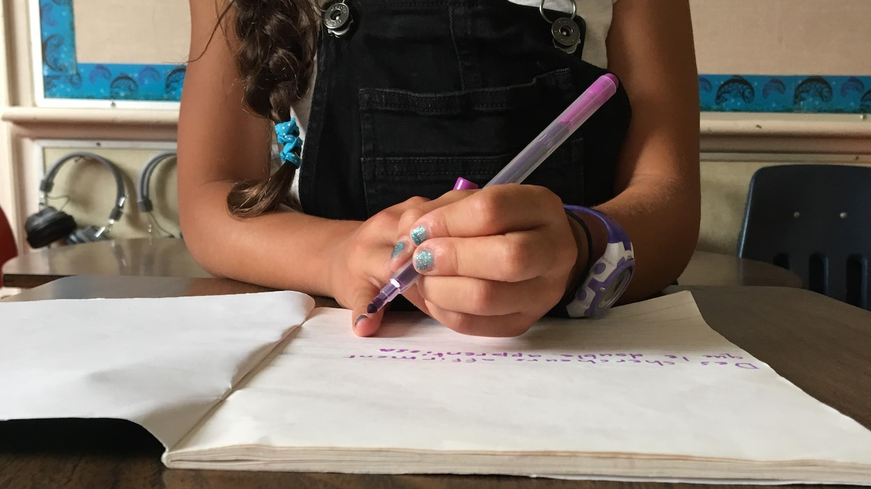 Une écolière inconnue écrit à la main dans un cahier.
