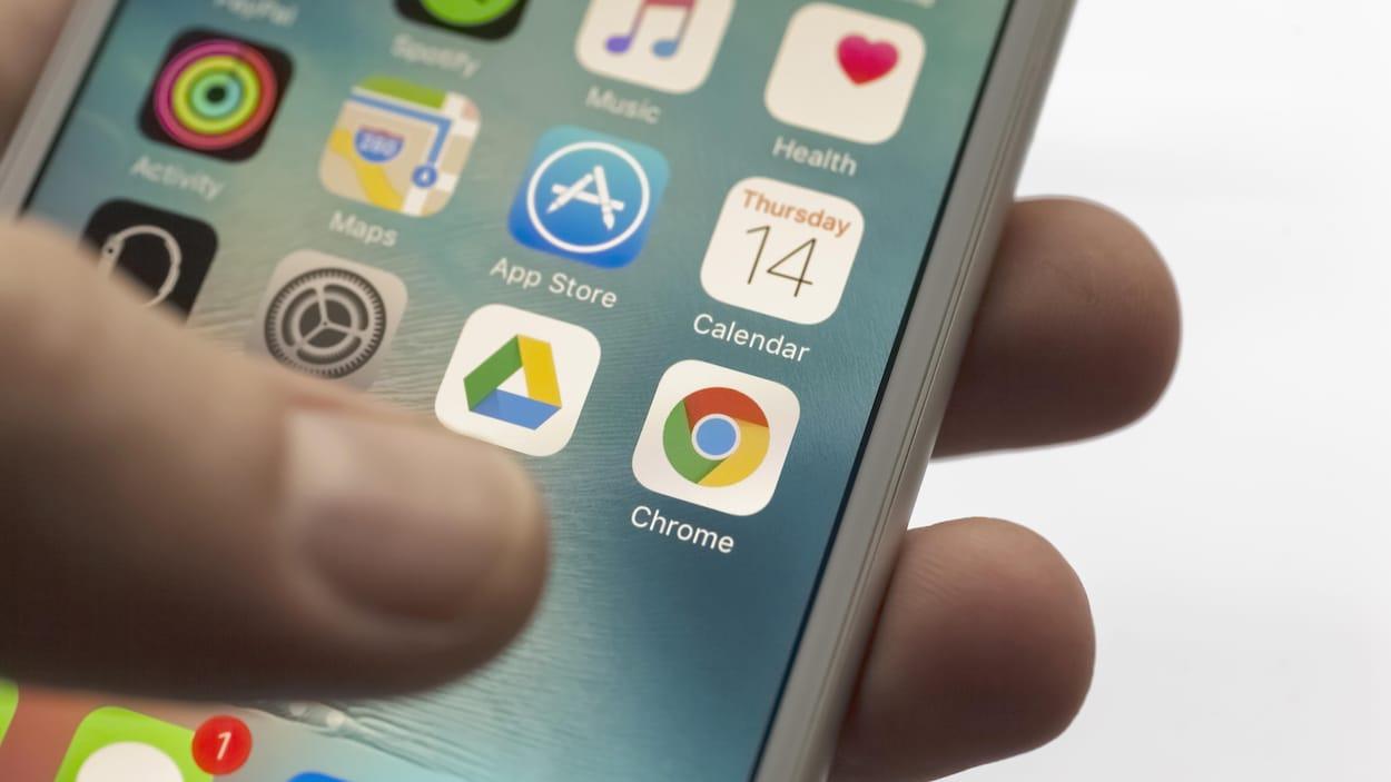 Une main tient un iPhone 6s. On voit l'écran d'accueil avec diverses applications.