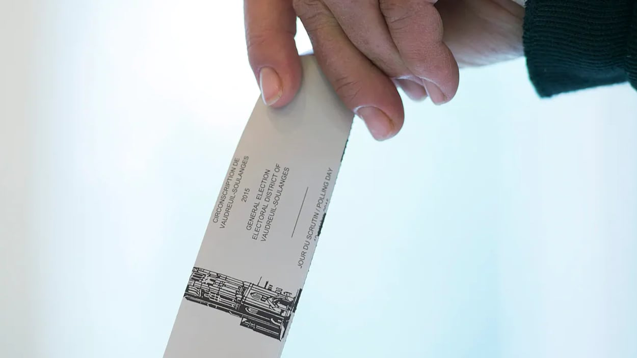 Une main tient un bulletin de vote.