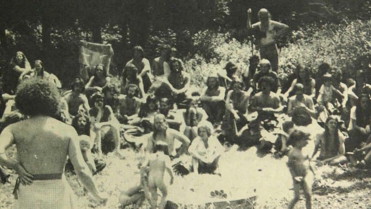 Photo en noir et blanc où on voit des enfants nus et des hippies en plein air.
