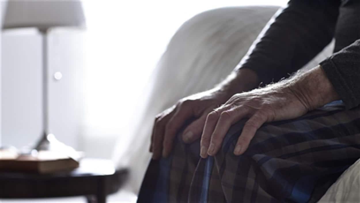Des mains d'un homme, assis sur la bord d'un lit, sont sur ses genoux.