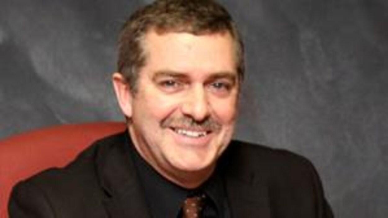 Un homme souriant photographié assis derrière une table.