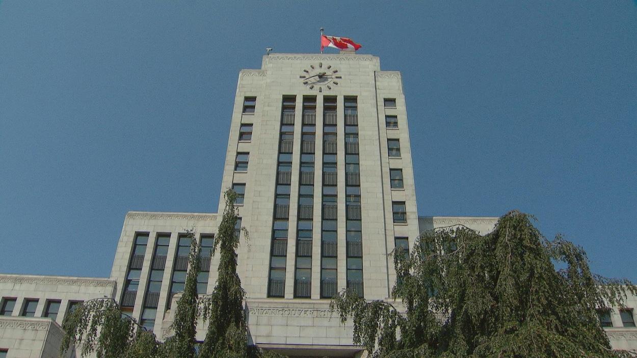 Plan en contre-plongée de l'hôtel de ville de Vancouver, un édifice en brique grise avec une imposante horloge et un drapeau canadien sur le toit.
