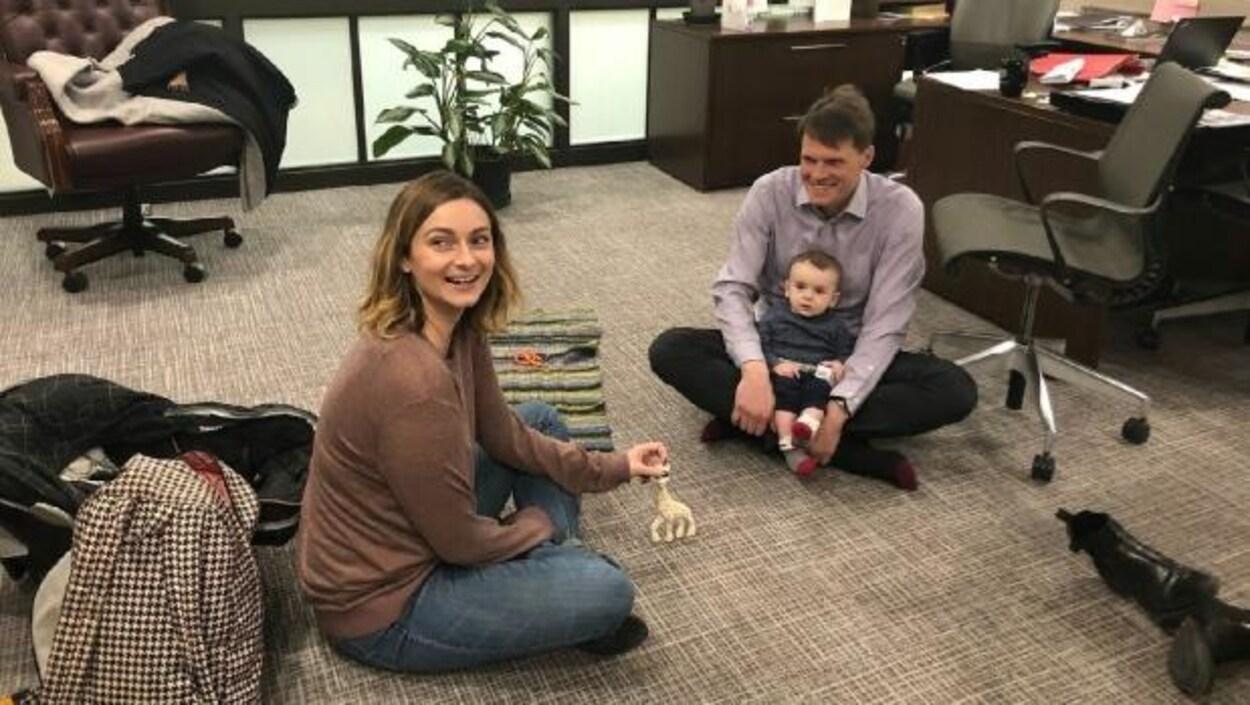 Mairin Loewen est assise par terre. Le maire de Saskatoon assis par terre en face d'elle avec le fils de cette dernière assis sur ses genoux.